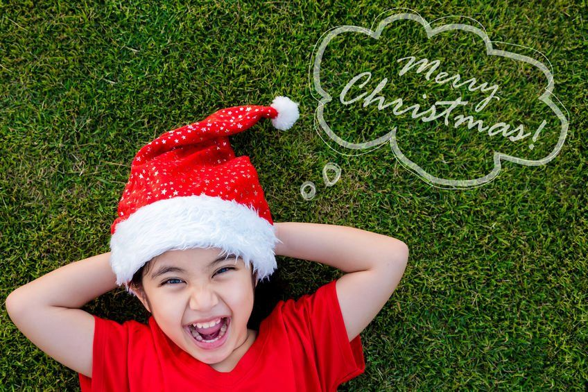 A school girl in red top & Santa Claus cap, lying down on green turf, smiling, her hands behind her neck.